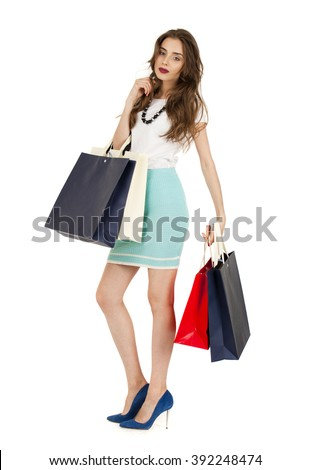 Fashion brunette woman portrait isolated. White background. Happy girl hold shopping bags. Female beautiful model