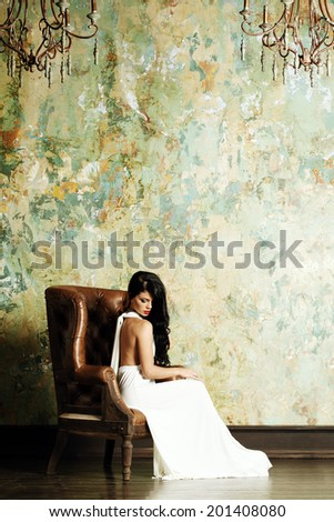 Fashion brunette woman posing in luxurious interior - stock photo