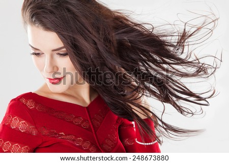 Fashion brunette woman with beauty long straight hair fluttering in the wind. Creative studio image over gray - stock photo