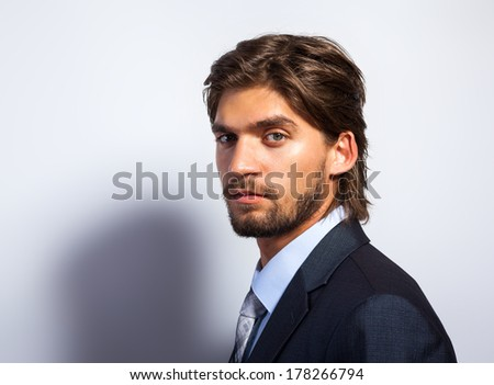 Fashion business man, Handsome serious male model face close up portrait, young businessman over gray background