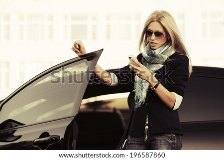 Fashion business woman calling on the phone at the car - stock photo