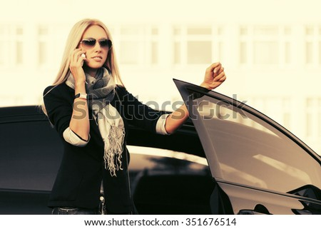 Fashion business woman calling on the phone by her car  - stock photo