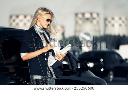 Fashion business woman with financial papers next a car  - stock photo