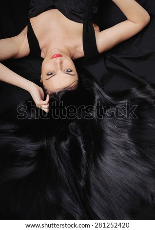 fashion chic woman with long bright black hair and silk shiny skin in studio on black background - stock photo
