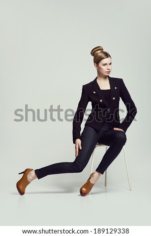 fashion classy woman sitting in the studio presenting shoes  - stock photo