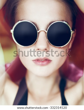 Fashion close-up portrait of a stylish woman with round glasses - stock photo