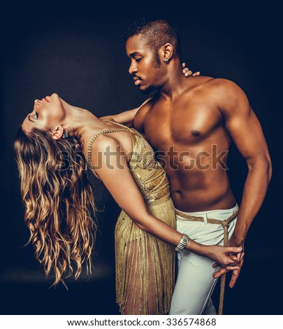 Fashion close up portrait of attractive dancing couple in sensual hugs. Holding hands. Dancing latino. Passion Love.  The girl's perfect skin facial make-up. The guy's pumped abs. Gold toned colors - stock photo