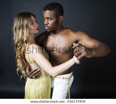 Fashion close up portrait of attractive dancing couple. Looking each other. Hugging, holding hands. Dancing latino. Passion, love. Sensuality. Girl's perfect skin facial make-up. The guy's pumped abs