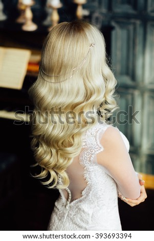 Fashion close up portrait of attractive young bride with long curly hair in morning of wedding day. Jewelry. Hairstyle. Vogue. Glamour Makeup. Fashionable blonde girl posing, looking away. Studio shot - stock photo