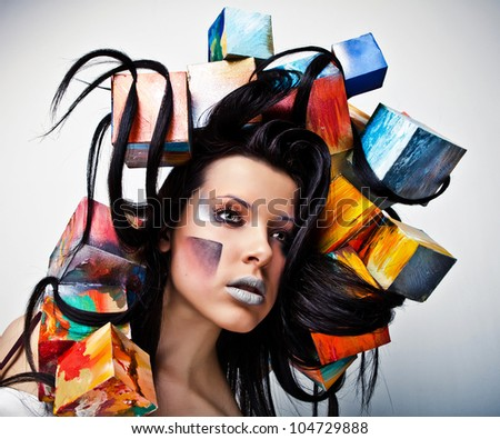Fashion close-up portrait of beautiful young girl with cubes on head. Conceptual photo.