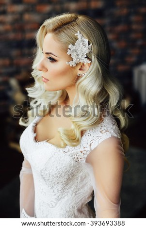 Fashion close up portrait of gorgeous young bride with long curly hair in morning of wedding day. Jewelry. Hairstyle. Vogue. Glamour Makeup. Fashionable blonde girl posing, looking away. Studio shot. - stock photo