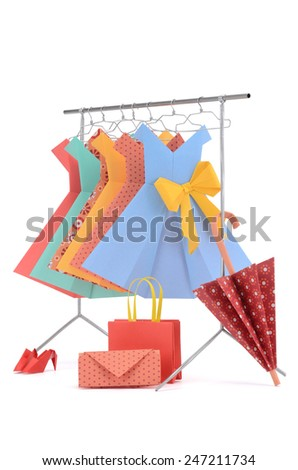 Fashion clothes: doll rack and hangers made of wire with ladies paper dresses, umbrella, purse, handbag and shoes isolated on white - stock photo