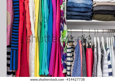 Fashion clothes in walk-in clothing closet or store display for shopping display. Colorful choices of trendy outfits well arranged in clean racks. Spring cleaning concept. Summer home living wardrobe. - stock photo