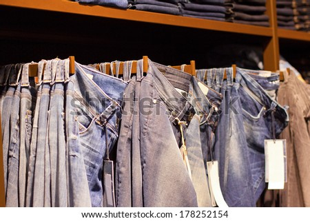 Fashion clothes on the shelves in the store. Jeans, shirts, pants hanging on hangers in the fashion store. Storefront, sale, shopping - stock photo