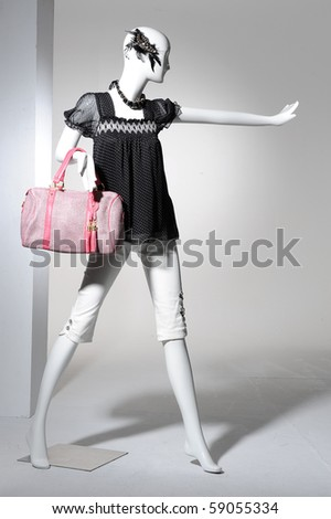 Fashion clothing on mannequin holding bag - stock photo