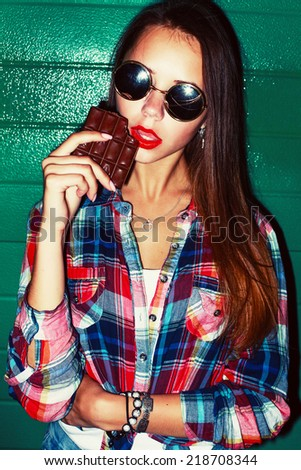 Fashion color vivid portrait of pretty young sexy girl having fun outdoor on the street in the night with red lipstick and eating chocolate  - stock photo