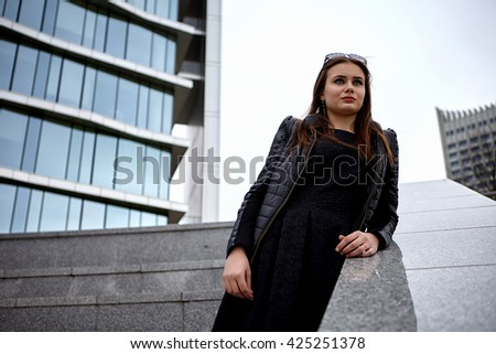 Fashion concept. Beautiful young woman in nice black coat. Posing on glass building.  City lifestyle. Female fashion.