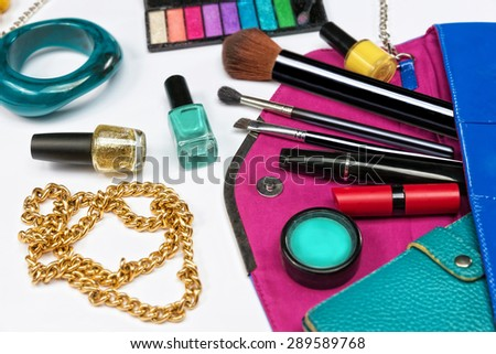 Fashion concept. Colorful make up items and wallet on top of the woman purse. - stock photo