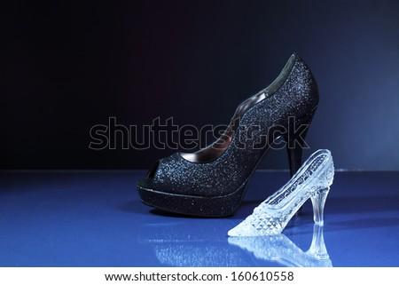 Fashion concept. Glass slipper near new black female shoe - stock photo
