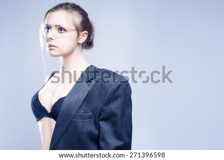 Fashion Concept: One Sexy and Sensual Caucasian Woman Dressed in Gray Suite Posing Against Gray Background.Horizontal Image Composition - stock photo