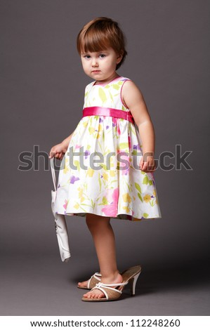 fashion-conscious little girl with big size shoes - stock photo