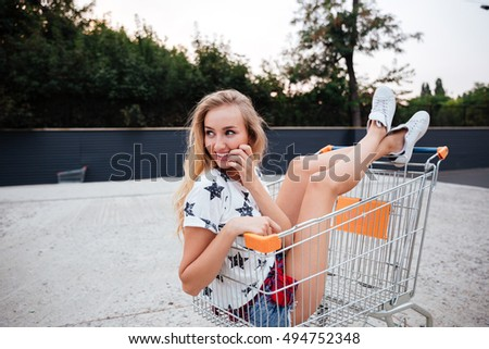 Fashion cool girl having fun sitting in shopping trolley cart outdoors