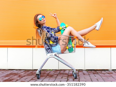 Fashion cool girl having fun sitting in shopping trolley cart with skateboard - stock photo