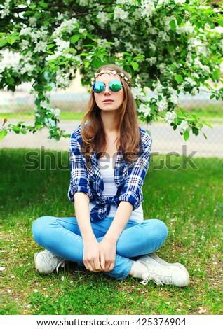 Fashion cool hippie woman sitting resting on grass in flowering garden - stock photo
