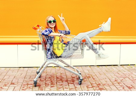 Fashion cool smiling girl having fun sitting in shopping trolley cart over colorful background - stock photo