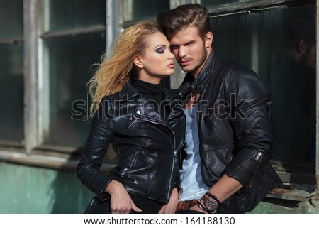 fashion couple in leather jackets posing against an old building outdoor - stock photo