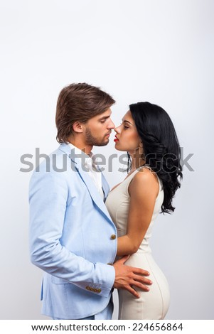 Fashion couple kissing, men wear blue suit and woman sexy dress over gray background