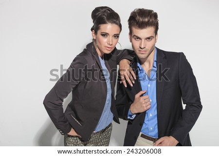 Fashion couple posing close to each other. The woman is holding her arm on his shoulder while he is fixing his jacket. - stock photo