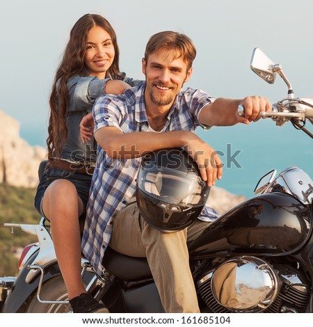 fashion couple sitting on a motorcycle - stock photo