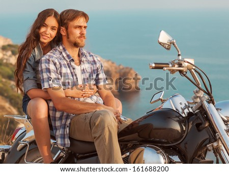 fashion couple sitting on a motorcycle at sunset - stock photo