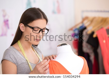 Fashion designer at work. Beautiful young woman in glasses working in fashion design studio - stock photo