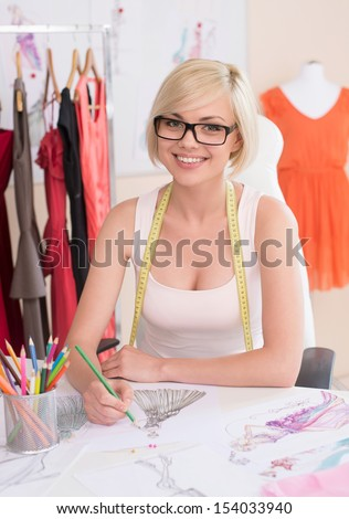 Fashion designer at work. Cheerful young fashion designer drawing sketch and smiling - stock photo