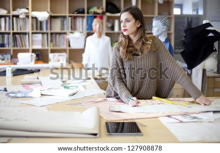Fashion designer daydreaming in the studio - stock photo