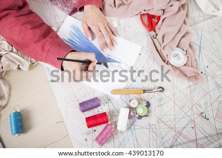 Fashion designer drawing in her fashion studio