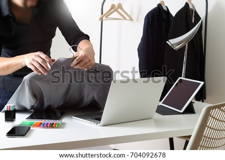 Fashion designer holding shirt and using laptop with digital tablet computer in modern studio