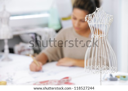 Fashion designer is drawing a fashion model - stock photo