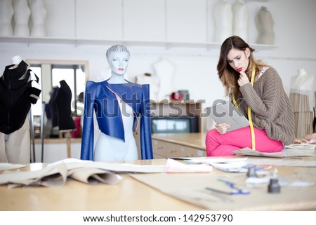 Fashion designer looking at designs on tablet computer. In the studio. - stock photo
