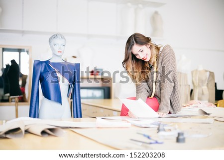 Fashion designer looking at sketches in studio