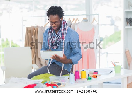 Fashion designer using digital tablet in a creative office - stock photo