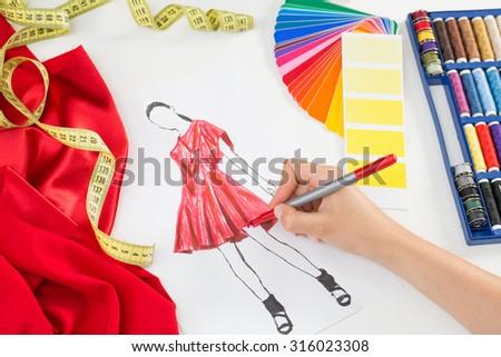 Fashion designer working in studio. Close up design. - stock photo