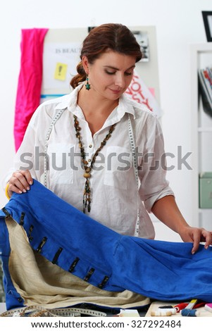 Fashion designer working in studio. Dressmaker woman