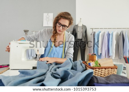 Fashion designer working on sewing machine in her studio