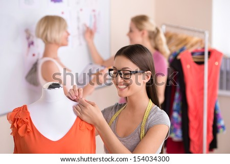 Fashion designers at work. Three beautiful young women in glasses working in fashion design studio - stock photo