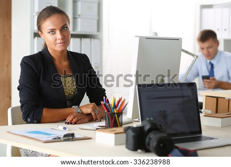 Fashion designers working in studio sitting on the desk