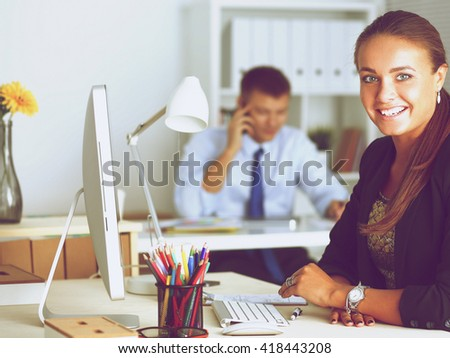 Fashion designers working in studio sitting on the desk - stock photo