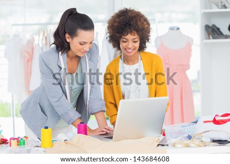 Fashion designers working on a laptop in a creative office - stock photo